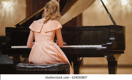 Close up view of cute teenager girl plays piano in the concert hall at scene