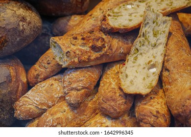 Close up view, cutting heap and stack of HELLAS-STANGE, wheat bread mixed with feta cheese, olive and paprika, and various type of rustic and crusty wheat breads at display of bakery store.