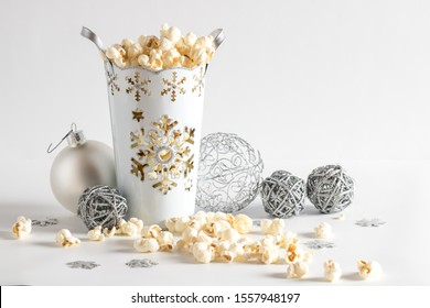 A close up view of a decorative vase filled with white cheddar popcorn and surrounded by Christmas ornaments.
