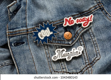 Close up view of denim jacket with cool graphic pins, funky hippie metallic fashion accessories, trendy artsy garment badges