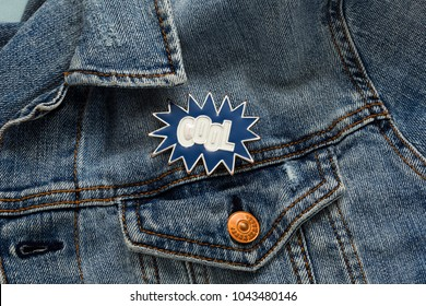 Close up view of denim jacket with cool cartoon graphic pin message, funky metallic brooch fashion accessory