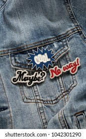 Close up view of denim jeans jacket with cool graphic pins, funky metallic brooch, fashion accessories