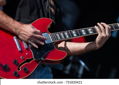 Close view detail of a guitar player playing on a concert