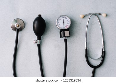 Close up view of device for measuring pressure, reflex hammer and stethoscope on glass surface