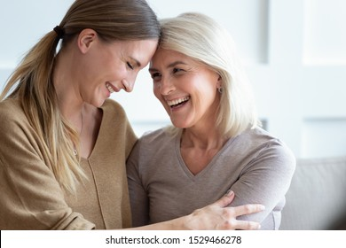 Close up view different generations beautiful women, aged mother and adult daughter touch foreheads laughing embracing sitting close to each other on couch, unconditional love, relative people concept