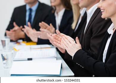 Close up view of diverse businesspeople in a meeting applauding and clapping their hands in recognition of an achievement or in praise