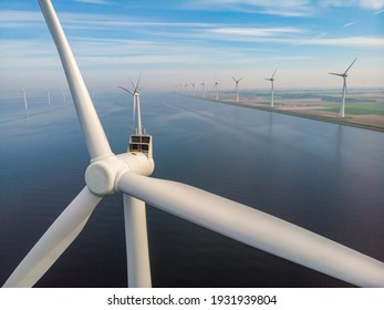 close view with drone at windmill park in the lake Ijsselmeer in the netherlands Noordoostpolder, Windmill turbines from above in Europe producing green energy