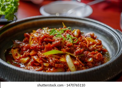 "Close up view of ""Dwaejigogi bokkeum"" or "" JEYUK BOKKEUM "" Korean style Spicy stir-fried pork on hot plate with various side dish in Korean restaurant."