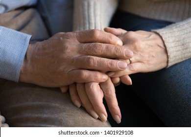 Close up view elderly spouses couple holding hands, husband and wife give each other help and psychological support, moral closeness symbol of devotion, forever lifetime love, sincere feelings concept