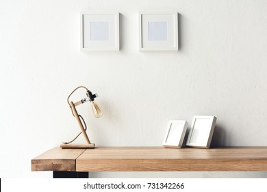 close up view of empty photo frames hanging on wall at workplace with table lamp