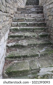Close up view of an exterior ancient staircase made of stone blocks. Old steps between two grey stone walls. Outdoors picture taken in the botanical park of Montpellier France. Symbol of direction.