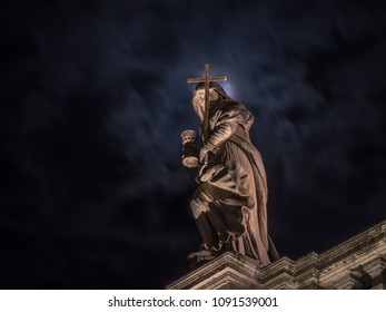 Close up view of the famous St. Blaise church personification of faith statue at the top of the church lit by lights from the square and the full moon from behind in the black night sky.