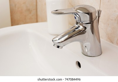 close up view of a faucet in a white sink