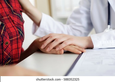Close up view of female doctor touching patient hand for encouragement, empathy, cheering, support after medical examination. Trust and ethics concept. Bad news, healthcare and medical service concept