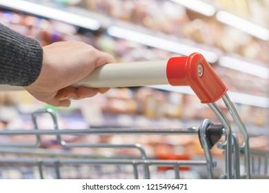 Close up view of a female hand with pushcart in supermarket. The racks with the consumer goods in blur. Shallow depth of field (toned)