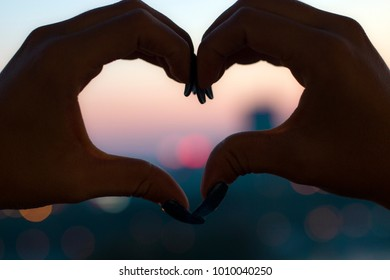 Close up view of female hands making heart shape during sunset