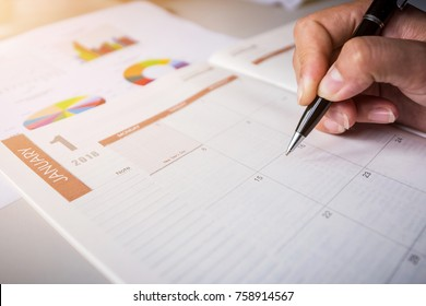 Close up view of female hands making notes in the blank calendar of a planner for 2018