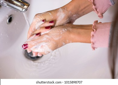 Close up view of female hands with red nails washing hands