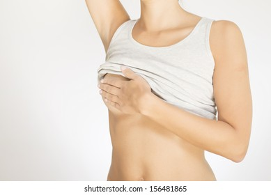 Close up view of the female torso with a grey shirt testing her breast for cancer flattening the tissue with one hand and manipulating to detect lumps with the fingers on her other hand