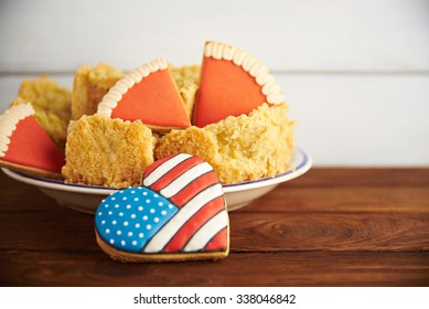 Close view at figures of gingerbread american flag in a heart shape with Thanksgiving pumpkin pie on a wooden backgroun