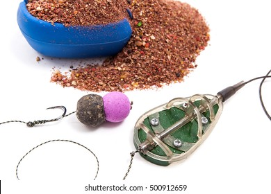 Close up view of fishing baits and Fishing gear for carp. Dry feed for carp fishing. Ready for use carp bait with fishing flat feeder for carp fishing isolated on white background.