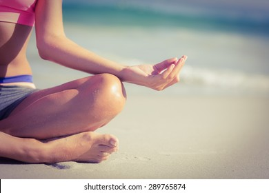 Close up view of fit woman doing yoga beside the sea at the beach