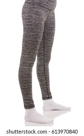 Close up view of fit woman legs wearing in grey sports thermal patterned pants in white socks from side view in standing foot to foot position