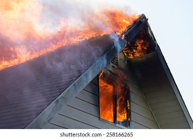 Close view of flames in an upper story window and running across the roof ridge.