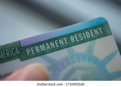 Close up view of Fragment of Permanent resident card (Green) card of USA on blurred background.