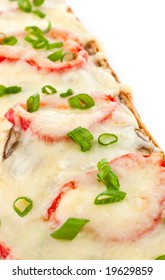 Close view of french bread pizza with red peppers, mushrooms, mozarella cheese and green onions