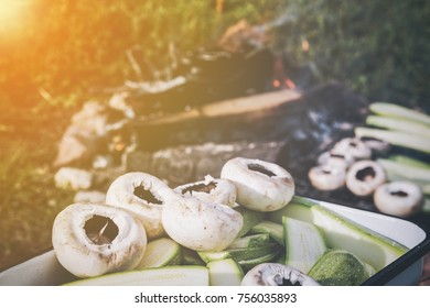 Close up view of fresh mushrooms and zucchini in a metal pan waiting to be grilled on an outdoor barbecue with burning wood coals with the sun glow in the left corner