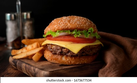 Close up view of Fresh tasty beef burger  and french fries on wooden tray with seasoning on rustic table