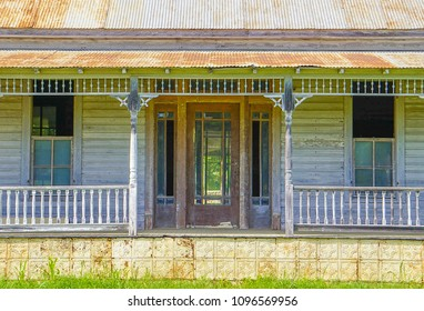 An up close view of the front door and porch of an old abandoned country farm house