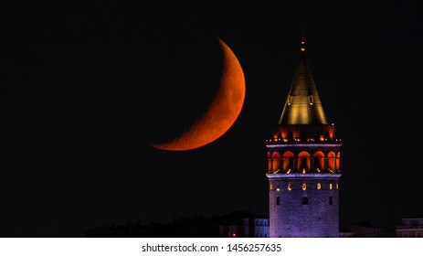 Close up view of galata tover and crescent moon on moonset. Galata tower under light. red moon.