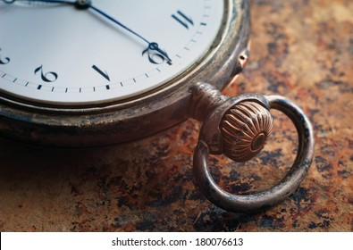 Close up view of the gears and mainspring in the mechanism of a silver pocket watch on old paper