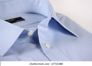 Close up view of a generic blue business shirt with a check pattern on a white background