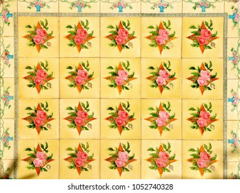 close up view of a geometric pattern created with ceramic tiles with a floral design on a yellow background