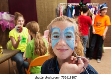 Close up view of girl getting her face painted while seated in a dressing room