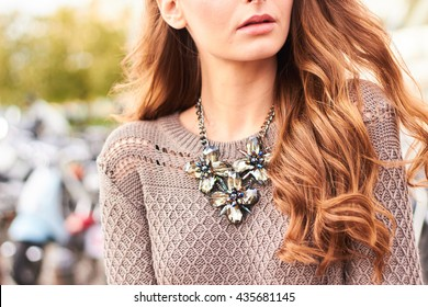 Close up view of a girl with long hair wearing a grey sweater and a necklace