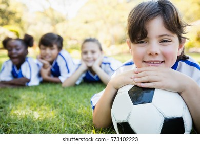 Close up view of girl lying on the floor with her soccer team in park
