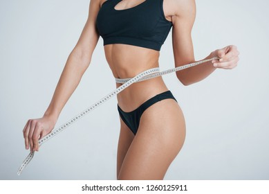 Close up view. Girl measures her waist standing in the studio with white background.