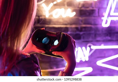 Close up view of girl woman female hands holding vr headset glasses device illuminated with futuristic purple neon lights, wearable virtual augmented reality digital innovation technology concept