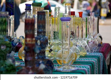 Close Up View of Glass Bongs on Flea Market Table, Sunlit Out of Focus Background and Backdrop