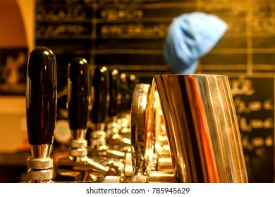 A close view of golden draft beer taps with black handles and a blue cap at the background