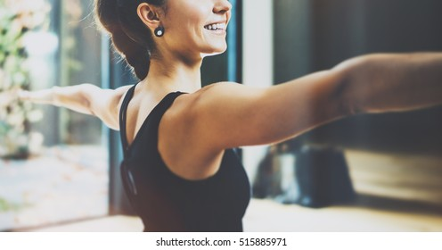Close up view of gorgeous young woman practicing yoga indoor. Beautiful girl practice Warrior Light asana.Calmness and relax, female happiness concept.Horizontal, blurred background