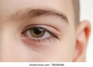 Close up view of a green boy's eye looking at camera