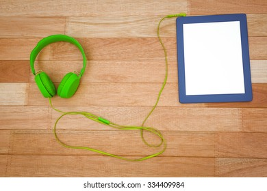 Close up view of a green headphone with a blue tablet