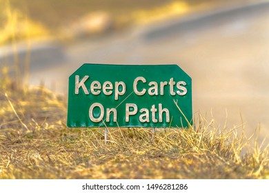 Close up view of a green and white sign that reads Keep Carts On Path