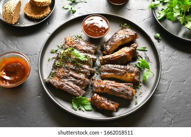 Close up view of grilled spare ribs on plate over black stone background. Tasty bbq meat.