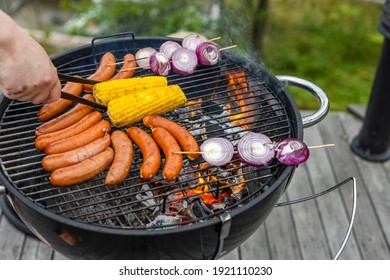 Close up view of grilling sausages, corn and onion outdoors on summer day. Healthy eating concept.